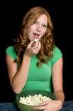 Menina que come a pipoca Fotografia de Stock
