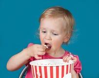 Menina que come a pipoca Foto de Stock