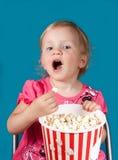 Menina que come a pipoca Foto de Stock Royalty Free