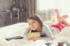 Menina que come a pipoca na cama Imagens de Stock Royalty Free