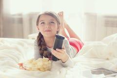 Menina que come a pipoca na cama Fotos de Stock