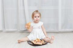 Menina que come a pizza Assento no assoalho fotos de stock