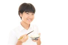 Menina que come um arroz Imagens de Stock