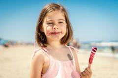 Menina que come um gelado colorido delicioso na praia Fotografia de Stock