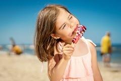 Menina que come um gelado colorido delicioso na praia Imagem de Stock Royalty Free