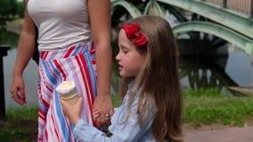 Menina que come um gelado, guardando a mão da mãe ver?o fora video estoque