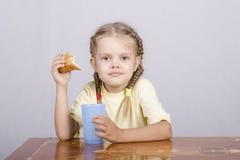 Menina que come um queque com suco na tabela Foto de Stock