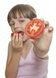 Menina que come um tomate Foto de Stock Royalty Free