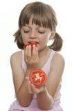 Menina que come um tomate Fotos de Stock Royalty Free