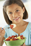 Menina que come uma bacia de salada da fruta fresca Fotografia de Stock