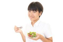 Menina que come uma salada Imagens de Stock