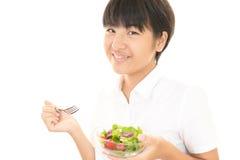 Menina que come uma salada Fotografia de Stock