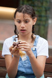 Menina que come uma torta de creme de Boston Fotos de Stock Royalty Free