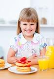 Menina que come waffles com morangos Fotografia de Stock