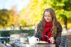 Menina que come waffles em um café exterior parisiense Foto de Stock