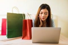 Menina que compra em linha na cama Foto de Stock