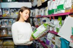Menina que compra o alimento seco para animais de estimação na loja Imagens de Stock