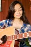 Menina que concentra-se em jogar a guitarra Fotografia de Stock