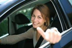 Menina que conduz o carro com atitude positiva Imagem de Stock Royalty Free