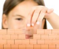 Menina que constrói uma parede Foto de Stock Royalty Free