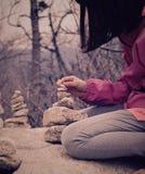 Menina que constrói uma torre de pedra Fotos de Stock