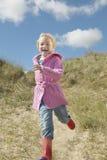 Menina que corre abaixo das dunas de areia Fotografia de Stock Royalty Free