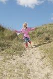 Menina que corre abaixo das dunas de areia Foto de Stock Royalty Free