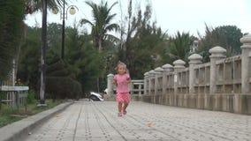 Menina que corre ao longo de um trajeto em um parque Menina no vestido que anda no passeio filme