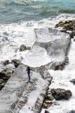 Menina que corre longe das ondas que espirram tudo em torno dela Fotos de Stock Royalty Free