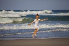 Menina que corre na praia Imagens de Stock Royalty Free