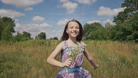 Menina que corre no prado com com o ramalhete das flores vídeos de arquivo