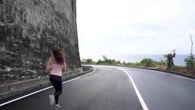 A menina que corre pela estrada rochosa no penhasco lavou pelo oceano video estoque
