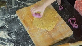 Menina que corta cookies de easter em uma massa filme