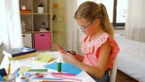 Menina que corta o papel da cor com tesouras em casa video estoque