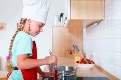 Menina que cozinha na cozinha moderna fotos de stock royalty free