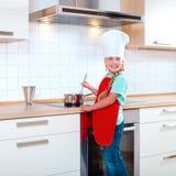 Menina que cozinha na cozinha moderna imagens de stock
