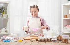 Menina que cozinha na cozinha home, fazendo pastelarias, conceito saudável do alimento Foto de Stock Royalty Free