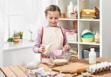 Menina que cozinha na cozinha home, fazendo pastelarias, conceito saudável do alimento Imagens de Stock
