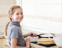 Menina que cozinha panquecas Fotografia de Stock Royalty Free