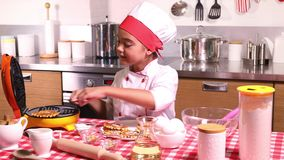Menina que cozinha waffles na cozinha filme