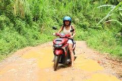 Menina que cruza a lagoa enlameada no velomotor imagem de stock royalty free
