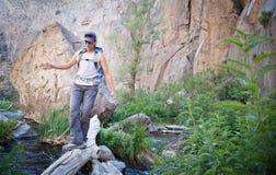 Menina que cruza uma ponte natural Fotos de Stock Royalty Free