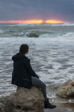 Menina que cumprimenta o mar tormentoso Imagem de Stock