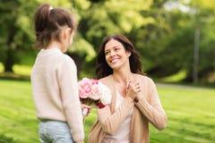 Menina que dá com as flores à mãe no parque do verão Imagens de Stock Royalty Free