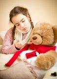 Menina que dá comprimidos ao urso de peluche doente Fotografia de Stock Royalty Free