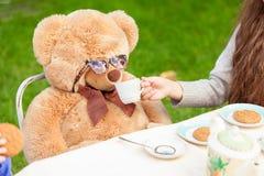 Menina que dá o chá ao urso de peluche na jarda imagem de stock