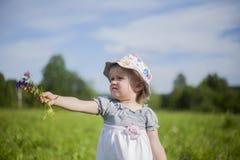 Menina que dá o grupo de flores Fotografia de Stock