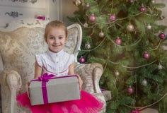 Menina que dá o presente sob a árvore de Natal imagens de stock