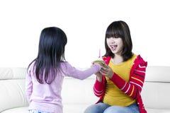 Menina que dá o queque a sua mãe fotografia de stock