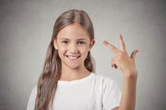 A menina que dá três dedos assina o gesto com mão imagem de stock